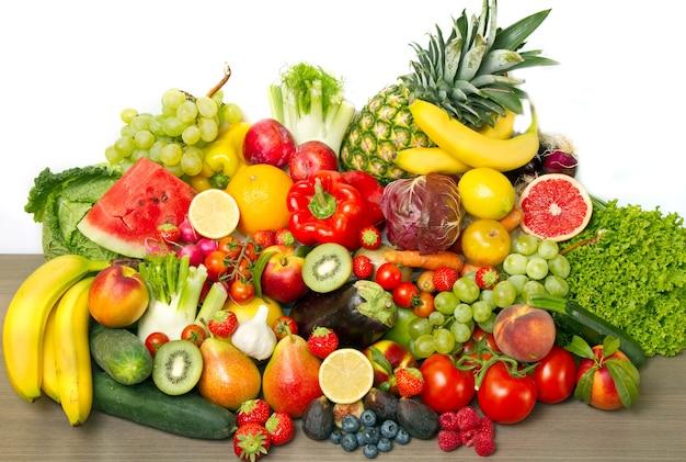 Fruit en groenten zoals tomaten, courgette, meloenen, bananen en druiven gerangschikt in een groep, natuurlijk stilleven voor gezond voedsel