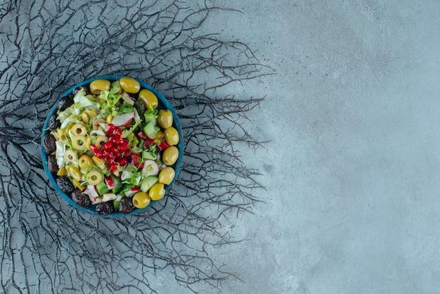 Fruit- en groentesalade met gemengde ingrediënten op blauw.