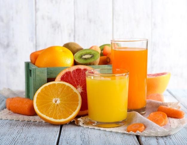 Fruit- en groentesap in glazen en vers fruit in vak op houten tafel op houten muur achtergrond