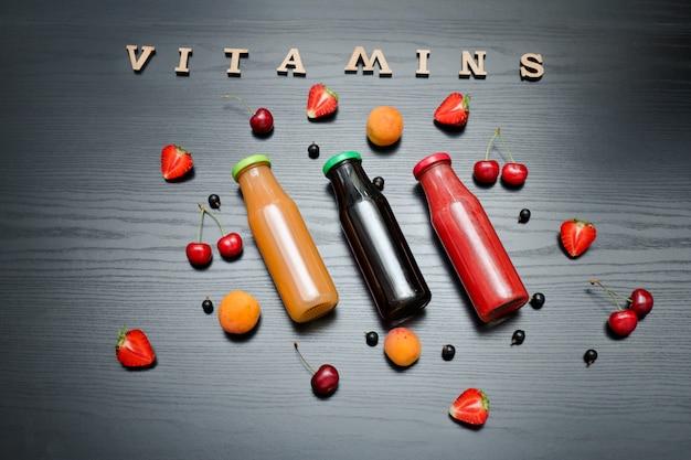 Fruit en inscriptie vitamines op een zwarte houten tafel. voedsel concept