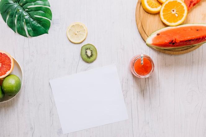 Fruit en smoothie in de buurt van papieren blad