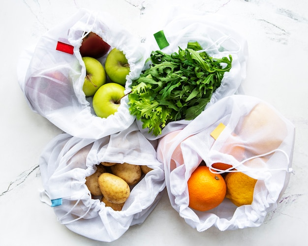Fruit en zomergroenten in herbruikbare milieuvriendelijke netzakken op marmeren tafel. zero waste shopping. ecologisch concept.