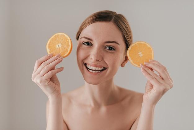 Fruit gebruiken voor huidverzorging. mooie jonge vrouw die een sinaasappelschijfje vasthoudt en naar de camera kijkt terwijl ze tegen de achtergrond staat
