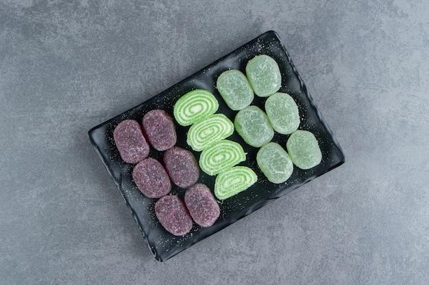 Fruit gelei zoete kleurrijke snoepjes op een donkere plaat