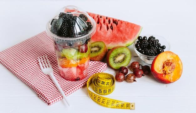 Fruit in een glas en een meetlint voor het meten van het lichaam