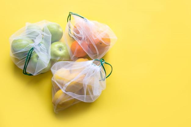 Fruit in herbruikbare milieuvriendelijke netzakken op geel.