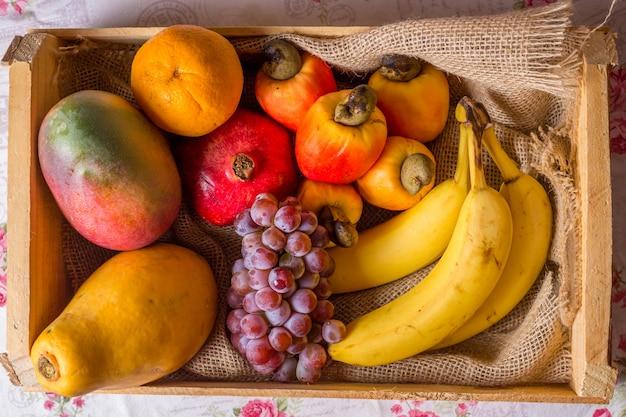 Fruit in houten mandje: cashewnoten, sinaasappel, druif, banaan, mango en papaja