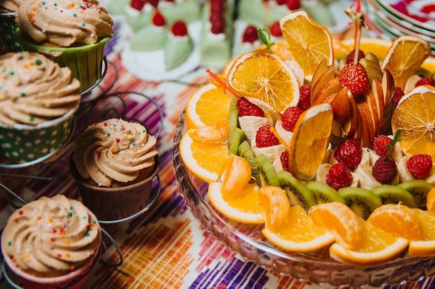 Fruit mix sinaasappel mandarijn kiwi banaan appel aardbei en framboos plakjes fruit op een bord muffins staan naast het fruit
