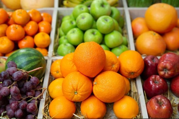 Fruit sinaasappel, banaan, appel, watermeloen, druiven op de toonbank van de winkel