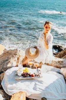 Fruit, snacks en drankjes tijdens picknick op zee. meisje doet cheatmeal aan zee kant met rotsen, gekleed in witte elegante jurk, strooien hoed. toerisme landbouw reis concept. reizen naar zuid-landen