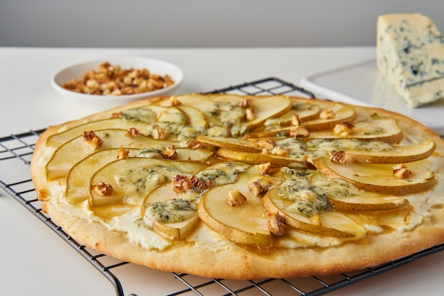 Fruit zelfgemaakte zoete perenpizza met kaas en honing, rustiek italiaans hartig voedsel met gebakjedeeg, zijaanzicht
