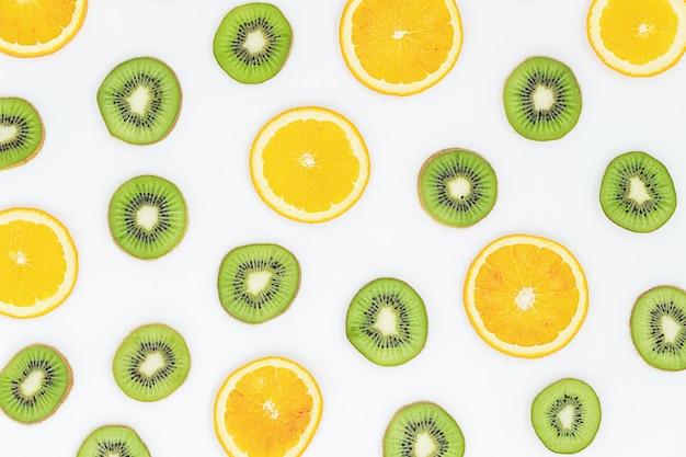 Fruitachtergrond van sinaasappelen en kiwiplakken op grijs oppervlak