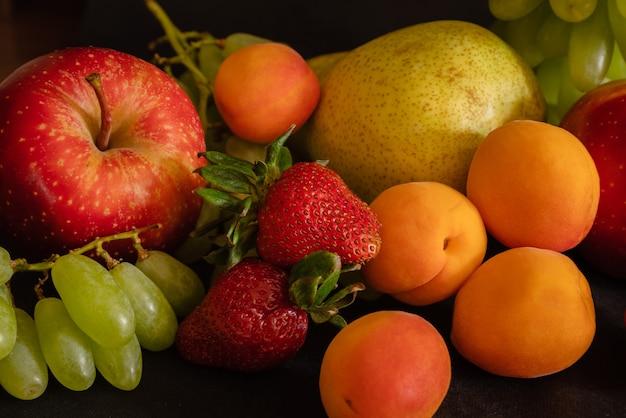 Fruitassortiment van vers fruit druiven aardbeien abrikozen peer appel op zwarte ondergrond