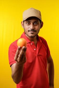Fruitbezorgingsconcept: indiase bezorger die oranje fruit in de hand houdt