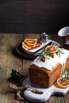 Fruitcake bestrooid met suikerglazuur, noten en droge sinaasappel op oude houten. kerst- en wintervakantie zelfgemaakte cake