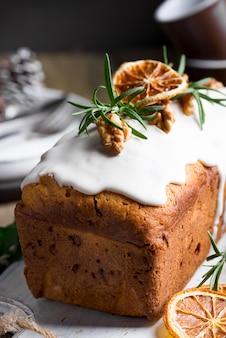 Fruitcake bestrooid met suikerglazuur, noten en droog oranje close-up. kerst- en wintervakantie zelfgemaakte cake