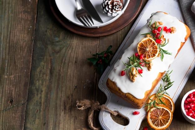 Fruitcake bestrooid met suikerglazuur, noten, pittengranaatappel en droge oranje oude houten. kerst- en wintervakantie zelfgemaakte cake