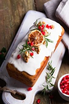 Fruitcake bestrooid met suikerglazuur, noten, pittengranaatappel en droog oranje close-up. kerst- en wintervakantie zelfgemaakte cake