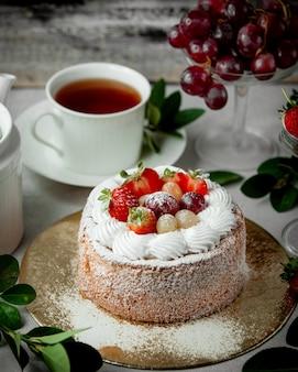 Fruitcake gegarneerd met aardbei witte en rode druif