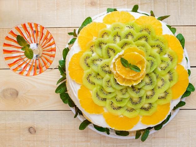 Fruitcake (sinaasappel, kiwi, munt) met een glas, close-up. bovenaanzicht