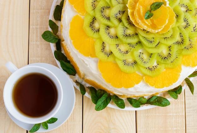 Fruitcake (sinaasappel, kiwi, munt) met een witte kop thee, close-up. bovenaanzicht