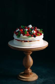 Fruitcake. taart versierd met bessen op houten standaard op zwart