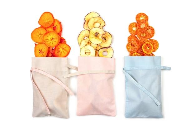 Fruitchips gemaakt van appels, mandarijnen, dadelpruimen en watermeloenen in linnen zakken op een wit oppervlak