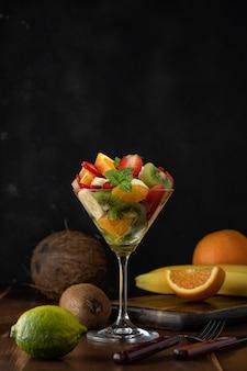 Fruitcocktail in martiniglas op houten tafel.
