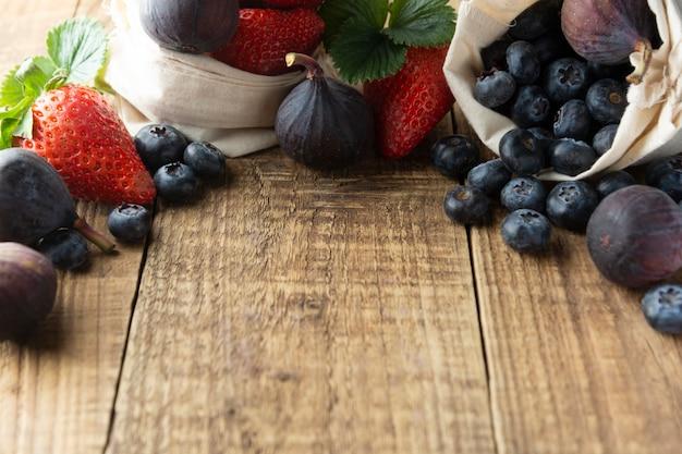 Fruitkader met aardbeien, bosbessen, fig. op rustieke geweven achtergrond.