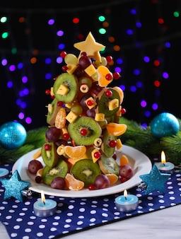 Fruitkerstboom op tafel op donkere ondergrond