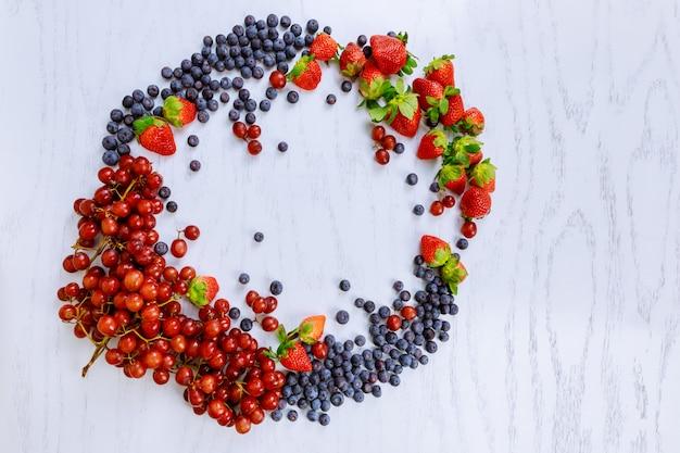 Fruitmand: aardbeien, bosbessen, braambessen, druiven