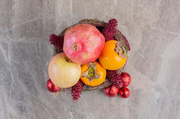 Fruitmand versierd met rode dennenappels en kerstboomversieringen op marmer.