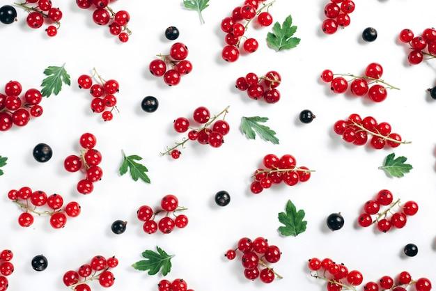 Fruitpatroon van verse bessen en groene bladeren op wit wordt gemaakt dat.