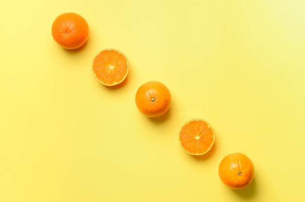 Fruitpatroon van verse oranje plakken op gele achtergrond. de helft van de citrus in een minimale platte lay-stijl.