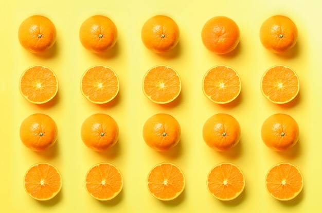 Fruitpatroon van verse oranje plakken op gele achtergrond. pop-artontwerp, creatief de zomerconcept. de helft van de citrus in een minimale platte lay-stijl.