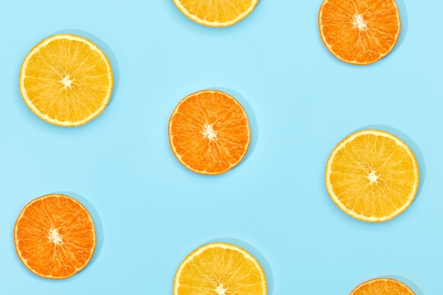 Fruitpatroon van verse rijpe schijfsinaasappel op blauwe achtergrond. bovenaanzicht