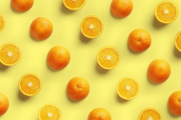 Fruitpatroon van verse stukjes sinaasappel op gele achtergrond. bovenaanzicht. kopieer de ruimte.