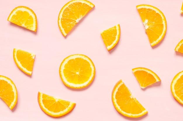 Fruitpatroon van verse stukjes sinaasappel op pastel achtergrond. bovenaanzicht.
