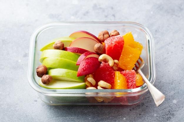 Fruitsalade en noten in een glazen container. gezond eten.