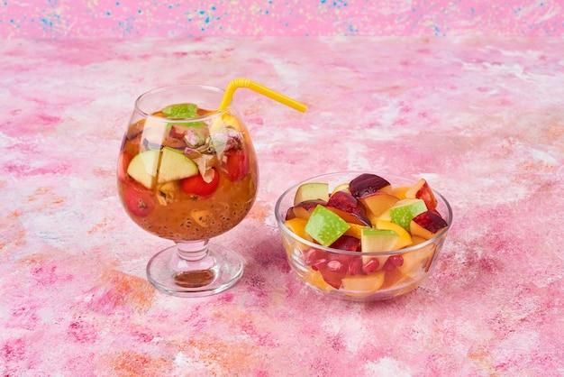 Fruitsalade in een beker met een glas cocktail.