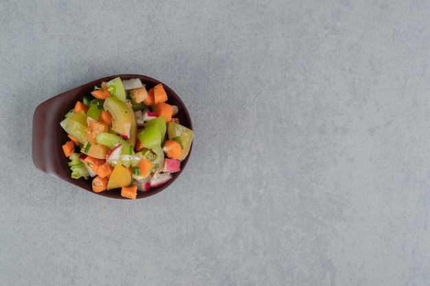 Fruitsalade in een bruine kop op betonnen tafel.
