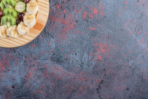 Fruitsalade in een houten schotel op blauwe achtergrond.