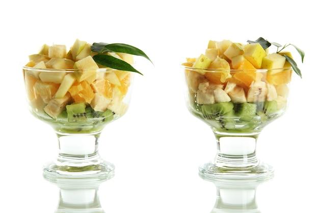 Fruitsalade in een ijscoupe op wit wordt geïsoleerd