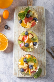 Fruitsalade in glazen, vers zomervoedsel, gezonde organische de ananaskokosnoot van de oranje kiwibosbessen