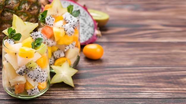 Fruitsalade in ruimte van het glas de houten exemplaar