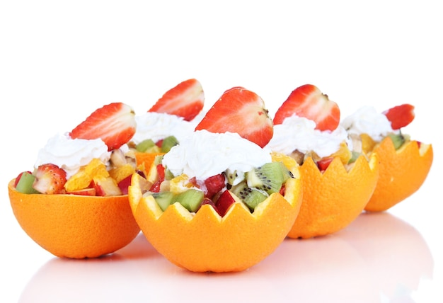 Fruitsalade in uitgeholde sinaasappel die op wit wordt geïsoleerd