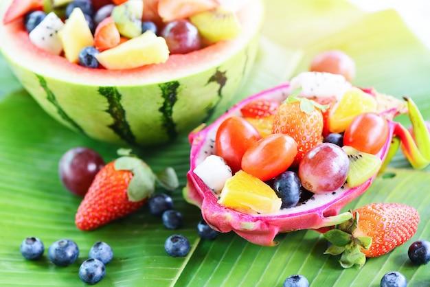 Fruitsalade kom geserveerd in een draak fruit en watermeloen groenten gezond voedsel aardbeien oranje kiwi bosbessen druif ananas tomaat citroen vers fruit tropisch op bananenblad