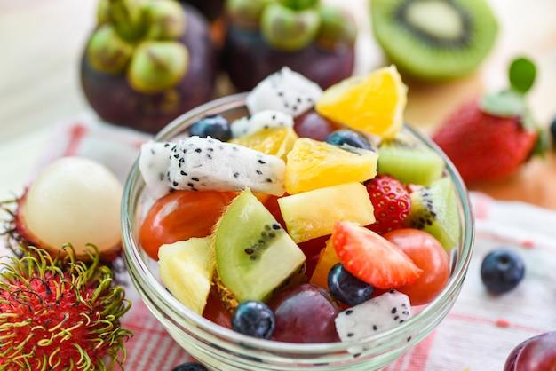 Fruitsalade kom verse zomer groenten en fruit gezond biologisch voedsel aardbeien sinaasappel kiwi bosbessen draak fruit tropische druif ananas tomaat citroen mangosteen rambutan