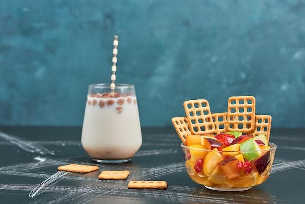 Fruitsalade met crackers en een kopje melk.