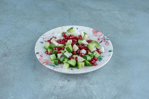 Fruitsalade met gehakte avocado en granaatappelpitjes.